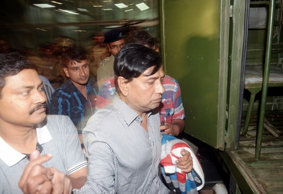 Police officers escort Chit-fund company Saradha Group's Chairman Sudipta Sen (R) to a police van outside the airport on his arrival in Kolkata.