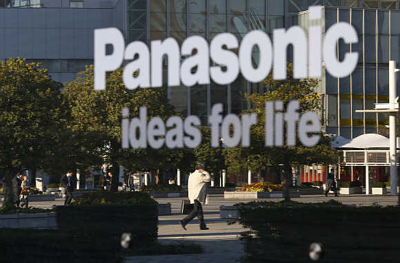 A man is reflected in a sign at Panasonic's showroom in Tokyo.