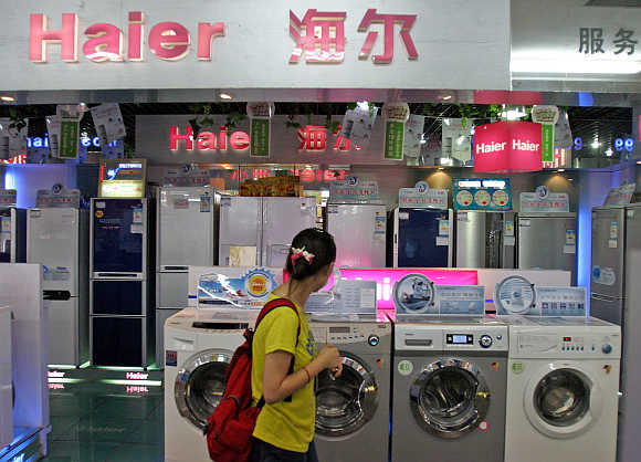 A woman walks past a Haier home appliance store in Shanghai.