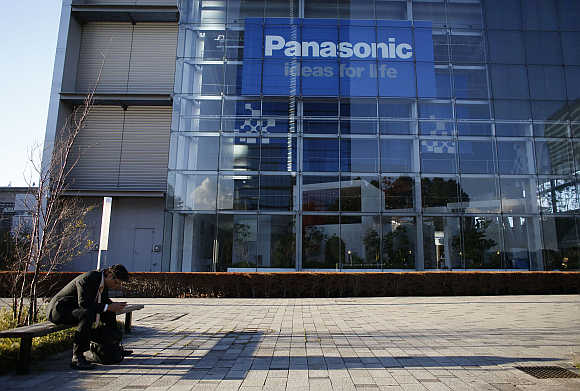 A man sits on a bench in front of Panasonic's showroom in Tokyo.