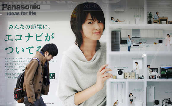 A man walks past an advertisement board of Panasonic outside an electronic shop in Tokyo.