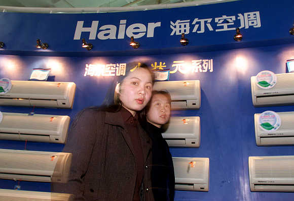 Women pass air conditioners made by China's Qingdao Haier Group in Beijing.