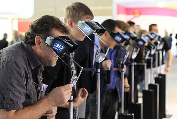 Visitors to Photokina look through 3-D glasses at the booth of Panasonic in Cologne, Germany.
