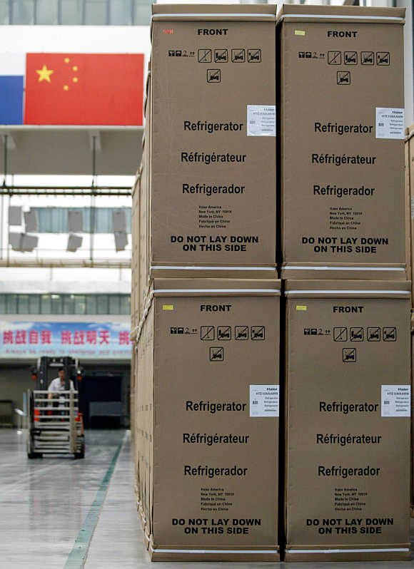 A worker operates a forklift past rows of refrigerators ready for shipment to the United States at Haier factory in China's eastern port city of Qingdao.