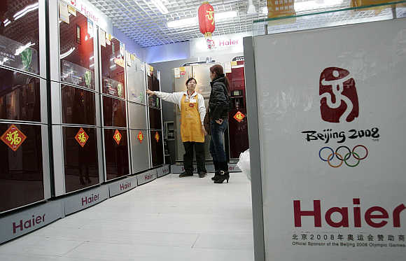 A salesperson recommends a refrigerator to a customer at a Haier store in Shanghai.