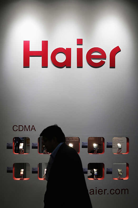 A visitor walks past CDMA mobile phones on display at Haier's exhibition pavilion in Singapore.