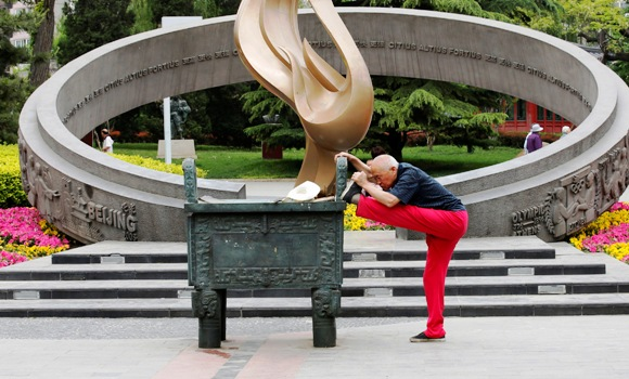An old man stretches at a park in Beijing.