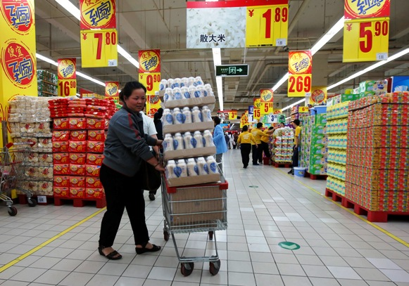A shopper pushes a cart loaded with beverage bottles at a supermarket in Beijing.
