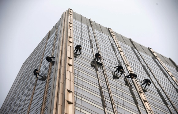Window cleaners work on a building during hazy conditions in Beijing.