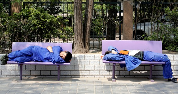 Workers take a nap on a bench in Beijing.