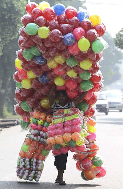 A vendor carries plastic balls for sale as he walks down the streets of Noida.