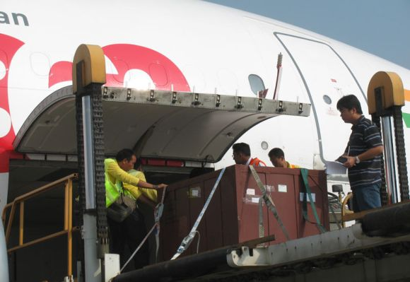 Workers load cargo in Deccan 360 aircraft.