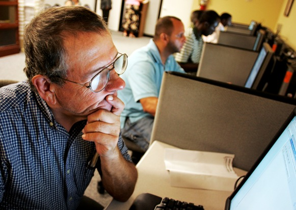 Stephen Battaglia (L) of West Palm Beach, Florida searches for jobs on a computer at Workforce Alliance in West Palm Beach, Florida.