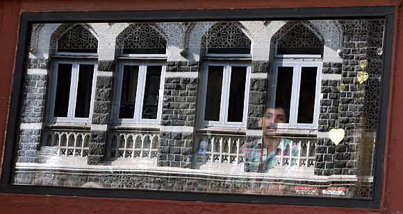 A man looks out of his shop as the Taj Mahal hotel is reflected in the window in Mumbai.