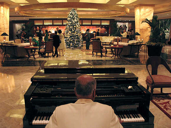 A man plays the piano at the lobby of Taj Mahal hotel in Mumbai.