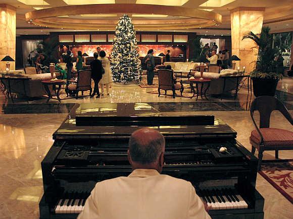A man plays the piano at the lobby of Taj Mahal hotel in Mumbai.