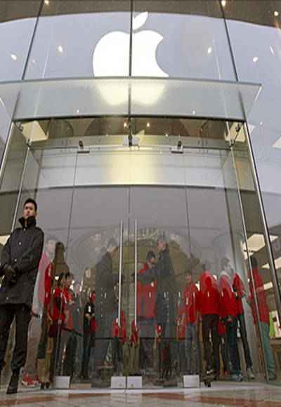 Security guards and staff stand at the entrance of an Apple store during the release of iPhone 5 in Beijing's Wangfujing shopping district.