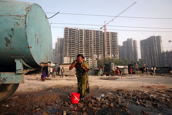 A labourer washes her face from a water tanker in front of residential apartments undergoing construction in Noida on the outskirts of New Delhi.