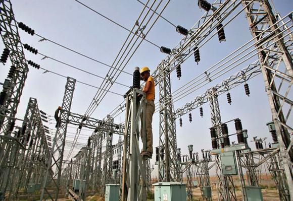 An employee works on electric pylons at a power station.