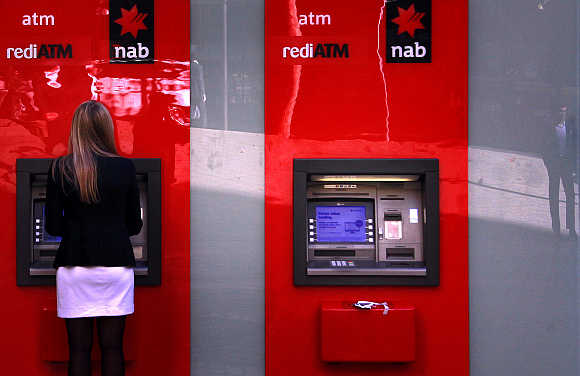 Man is reflected in a glass panel next to a woman using a National Australia Bank automated teller machine in central Sydney.