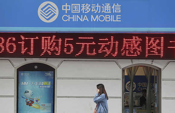 A woman walks past a branch of China Mobile in Wuhan, Hubei province, China.