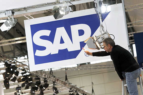 A worker adjusts a spotlight at the SAP booth in Hannover, Germany.