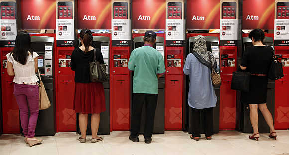Customers use automated teller machines outside a branch of Development Bank of Singapore.