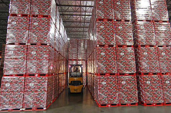 A worker drives a forklift between cases of Coca-Cola in a warehouse at the Swire Coca-Cola facility in Draper, Utah, United States.