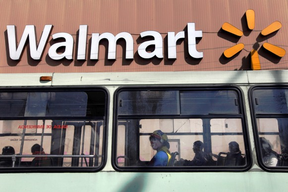 A clown sits inside a bus seen in front of a Wal-Mart store in Mexico City.