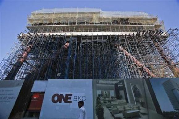 A man walks in front of the under-construction One BKC commercial complex, being built by The Wadhwa Group, in the Bandra-Kurla Complex in Mumbai.