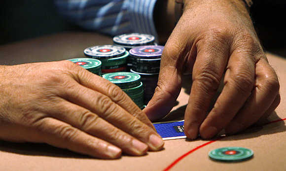 A contestant covers his cards during the Poker Stars tournament in London.
