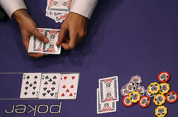 A dealer lays a playing card on the table at the World Series of Poker Europe competition at the Empire Casino in London.