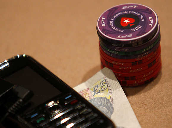 Chips are stacked up next to a five pound note and mobile phone during the Poker Stars tournament in London.