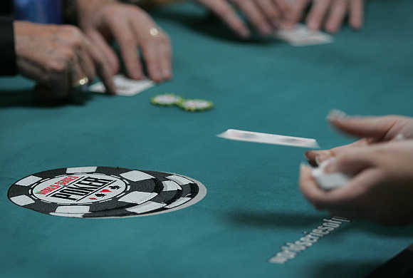 A dealer tosses out a card in the $10,000 buy-in, no limit Texas Hold 'Em main event during the World Series of Poker at the Rio All-Suite Hotel & Casino in Las Vegas, Nevada, United States.