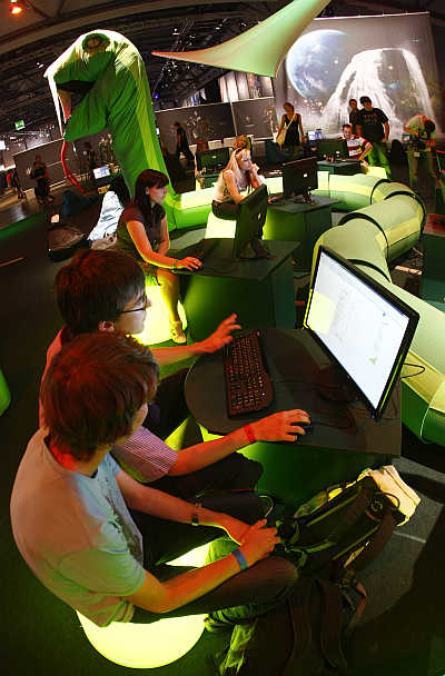Visitors play at an exhibition stand at the Games Convention Online fair in the eastern German city of Leipzig.