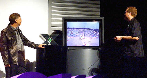 Bill Gates, left, watches as Seamus Blackley, Director of Microsoft's X-Box advanced technology, demonstrates the capabilites of the video game console at the Game Developers Conference in San Jose, California.