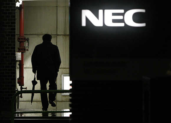 A man walks in front of the headquarters of NEC in Tokyo.