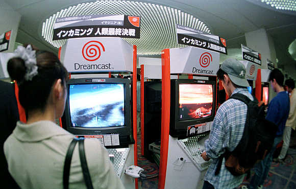 Young Japanese try out computer game maker Sega Enterprises' Dreamcast game machines at a Tokyo hotel.