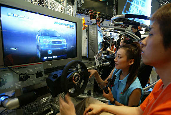 Visitors play Gran Turismo 4 video game on Sony Playstation 2 at Tokyo Game Show in Chiba, Japan.