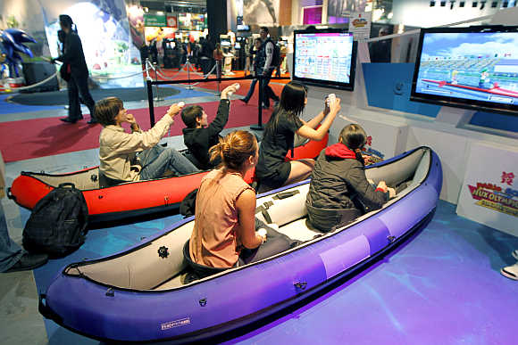 Visitors play a rowing race with Nintendo Wii games during a visit at the Paris Games Week show.