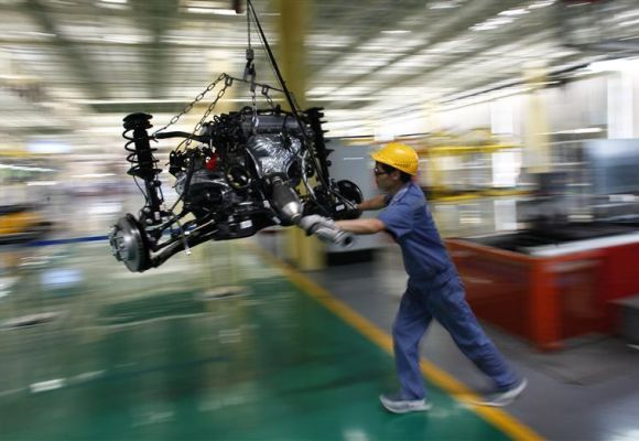 An employee pushes a car engine at a Geely Automobile assembly line in China.