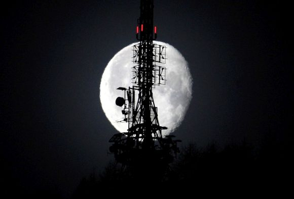 The waning gibbous moon shines behind a telecommunications tower.