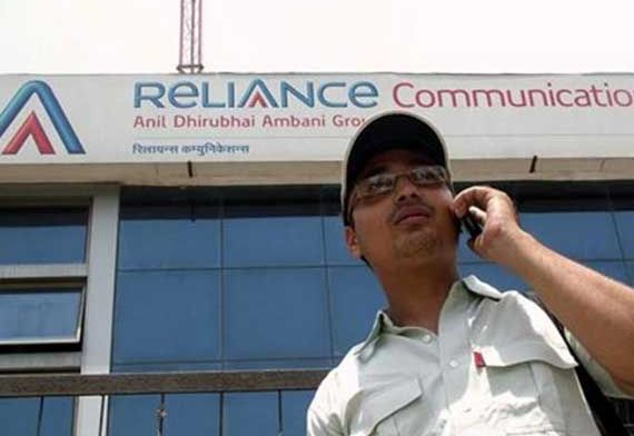 A man talks on a mobile phone in front of an advertisement for Reliance Communications.