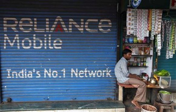 A street vendor sells his goods beside a Reliance mobile phone store.