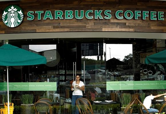 A customer with a cup of coffee leaves the new Starbucks store.