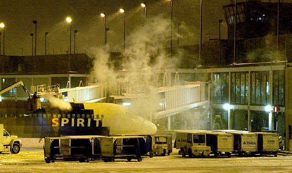 Ground crew de-ices a Spirit Airlines jet outside Terminal 3 at O'Hare International Airport in Chicago.