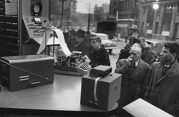 A group of men look at computers in a shop window in 1955.