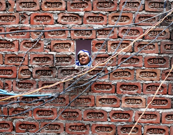 A woman looks from behind a brick wall of her house in the old quarters of Delhi.