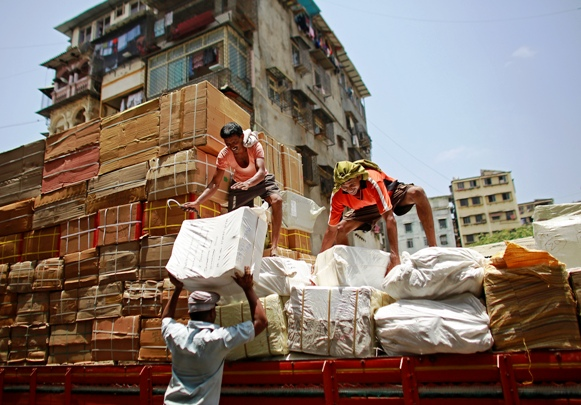 Workers of a transport company load packages on a truck at a wholesale market in Mumbai.