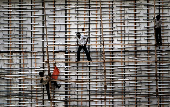 Workers install bamboo poles on a billboard under construction along a road on the outskirts of Ahmedabad.